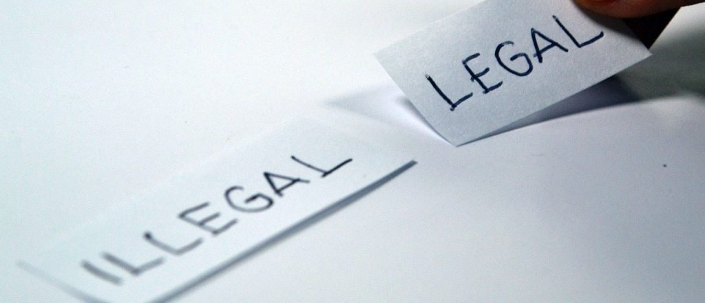 Photo of pieces of paper with the words illegal and legal
