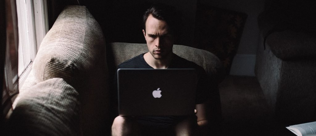 Photo of guy sitting on a couch using a laptop computer
