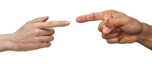 Photo of man and women's hands pointing fingers at each other